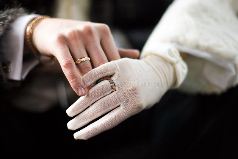 Le mani enamoured con l'anello di cerimonia nuziale fotografia stock