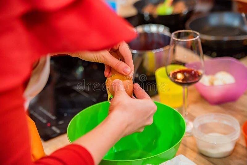 Le mani femminili aggiungono l'uovo in ciotola di plastica immagini stock libere da diritti