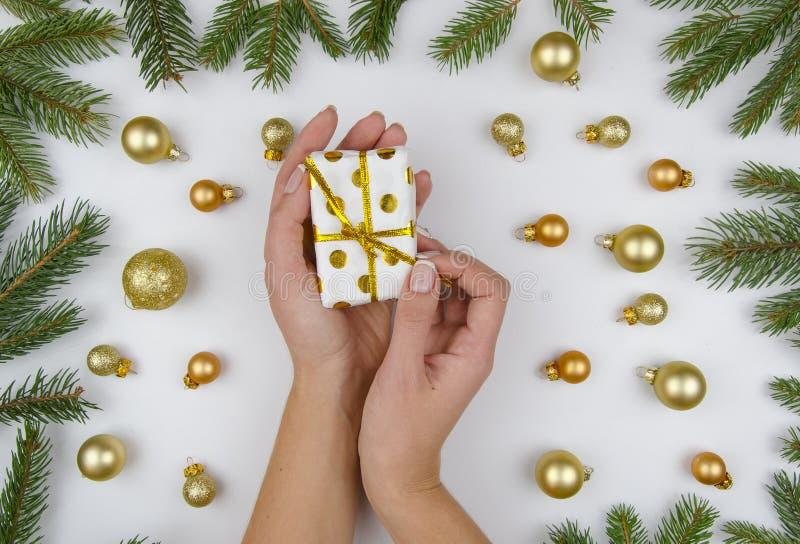 Le mani femminili apre un piccolo contenitore di regalo su fondo bianco con le palle dorate di natale ed i rami verdi dell'abete  immagini stock