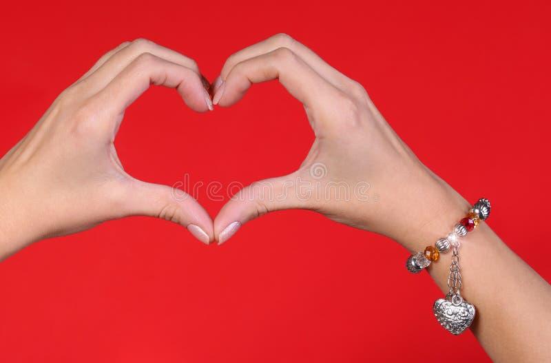 Le mani femminili che fanno un cuore modellano sopra rosso fotografia stock libera da diritti