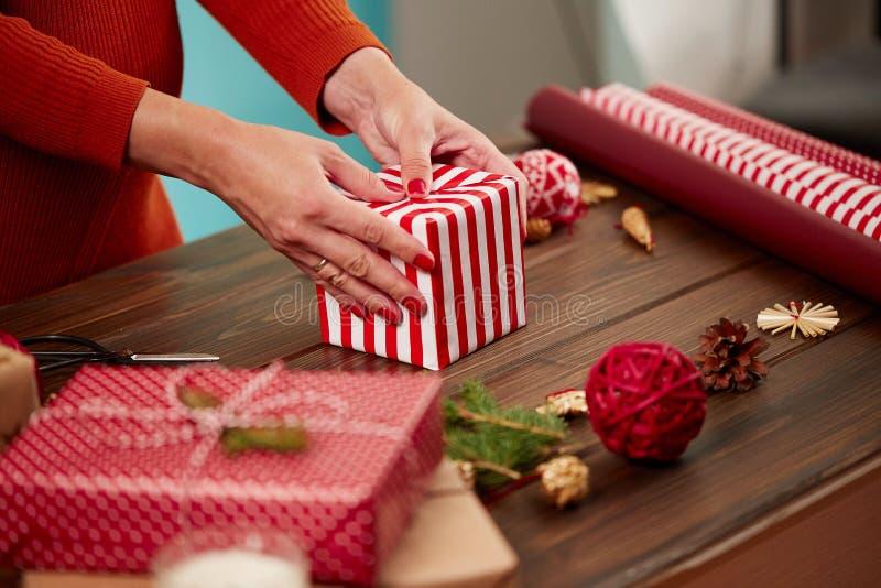 Le mani femminili che imballano il giftbox nel Natale spogliato hanno colorato la carta fotografie stock libere da diritti