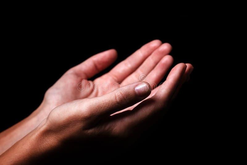 Le mani femminili che pregano con le palme su arma steso Priorità bassa nera fotografia stock