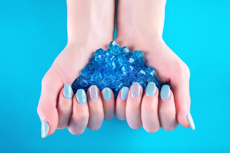 Le mani femminili con il manicure blu sul dito inchioda tenendo molto la pietra preziosa decorativa fotografie stock