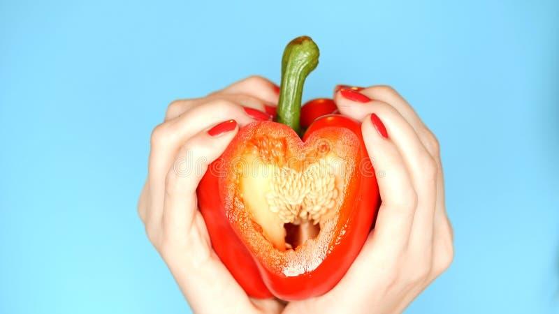 Le mani femminili con il manicure rosso tengono il peperone dolce rosso a disposizione sotto forma di cuore su un fondo blu fotografie stock libere da diritti