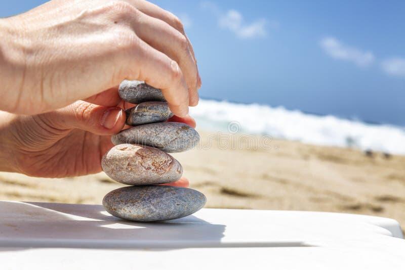 Le mani femminili costruiscono un cairn sulla spiaggia fotografia stock