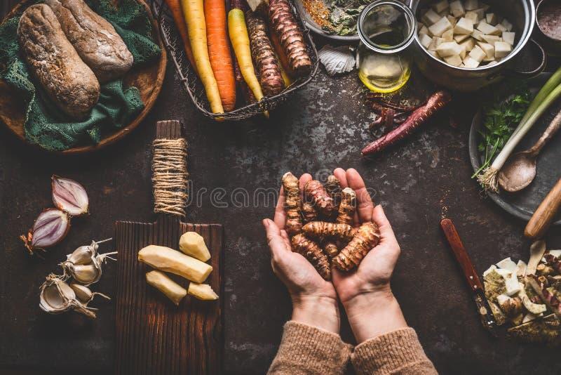 Le mani femminili della donna che tengono i topinambur o le verdure della pera della terra sul tavolo da cucina rustico con la co immagini stock libere da diritti