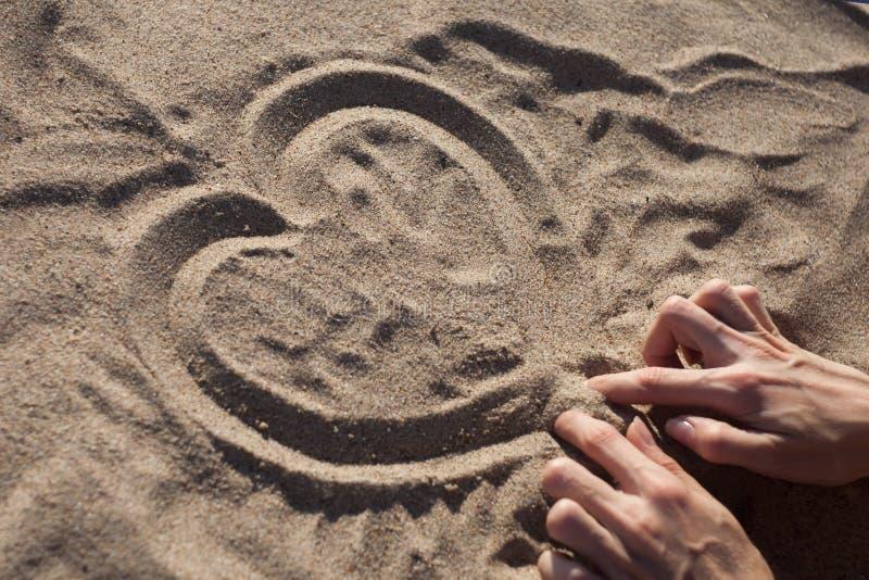 Le mani femminili disegnano il cuore sulla sabbia asciutta sulla spiaggia un giorno soleggiato fotografia stock libera da diritti