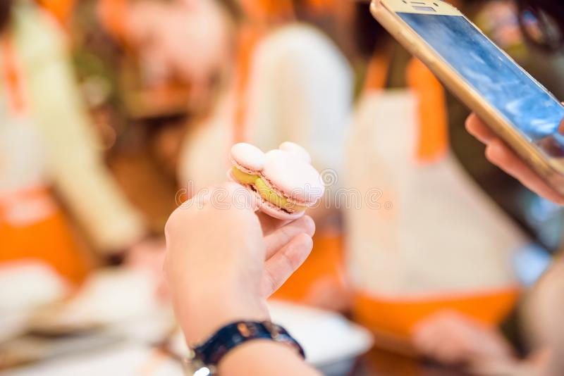 Le mani femminili hanno un il macaron francese immagine stock