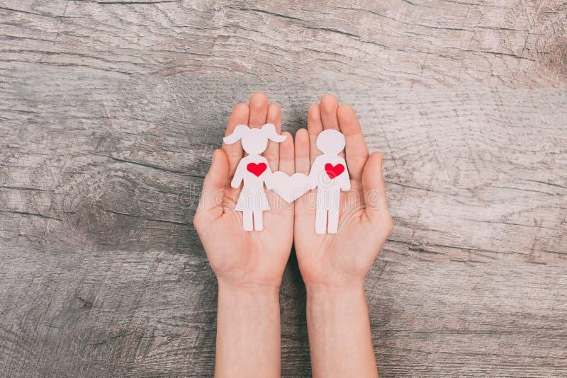 Le mani femminili mostrano due genti di carta, un uomo e una donna, su un fondo di legno fotografia stock