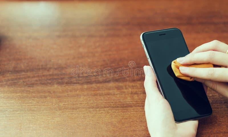 Le mani femminili puliscono lo schermo dello smartphone con un panno arancio Preoccupandosi per gli aggeggi Copi lo spazio immagini stock libere da diritti