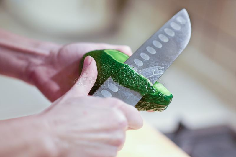 Le mani femminili sbucciano l'avocado organico fresco con il coltello in cucina fotografie stock