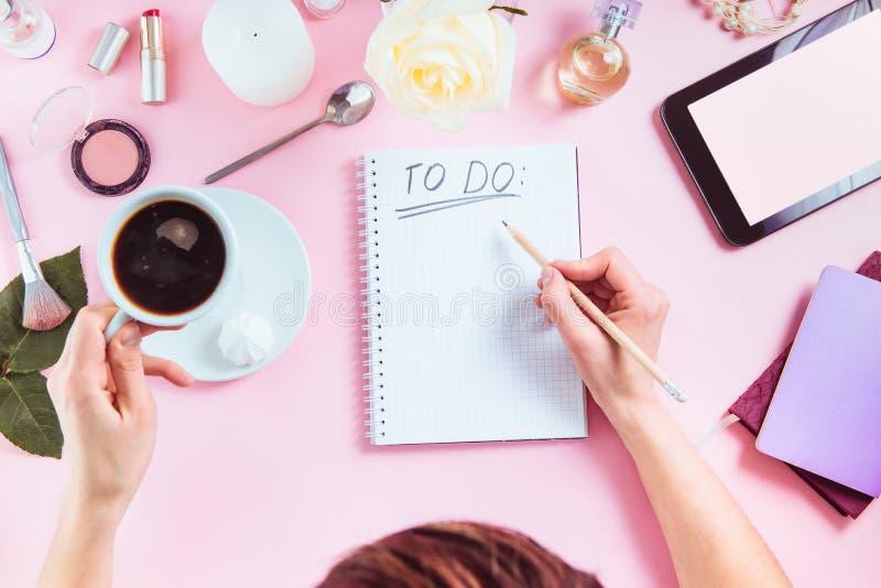 Le mani femminili scrivono per fare la lista sui precedenti rosa con i cosmetici, la tazza di caffè, i taccuini, compressa con lo fotografia stock libera da diritti