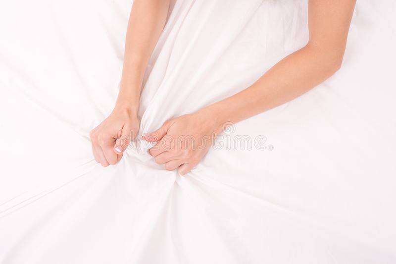 Le mani femminili sgualciscono lo strato bianco, donna che fa il sesso, fuoco sulle mani fotografia stock libera da diritti