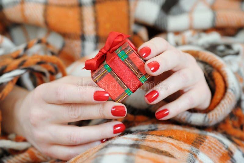 Le mani femminili si chiudono sulla tenuta del regalo immagini stock