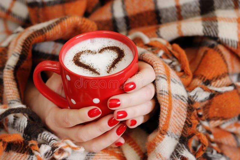 Le mani femminili si chiudono sulla tenuta della tazza rossa con cuore fotografia stock libera da diritti