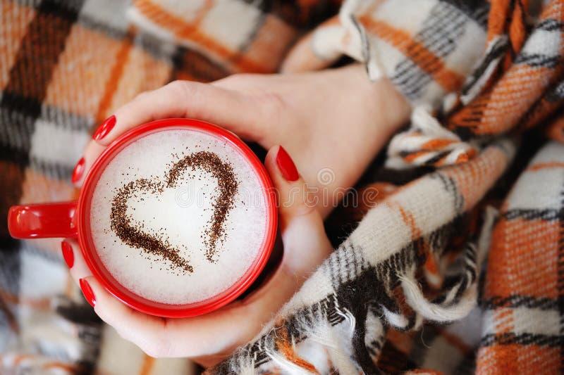 Le mani femminili si chiudono sulla tenuta della tazza rossa con cuore immagine stock