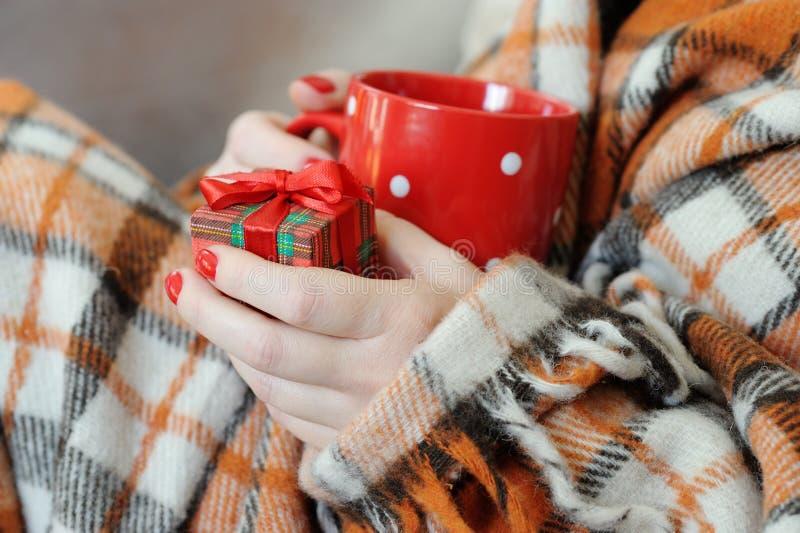 Le mani femminili si chiudono sulla tenuta un regalo e della tazza rossa fotografia stock libera da diritti