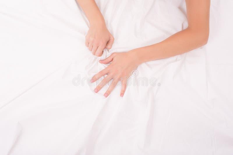Le mani femminili sopra sgualciscono lo strato bianco, coppia facendo sesso, fuoco sulle mani immagine stock