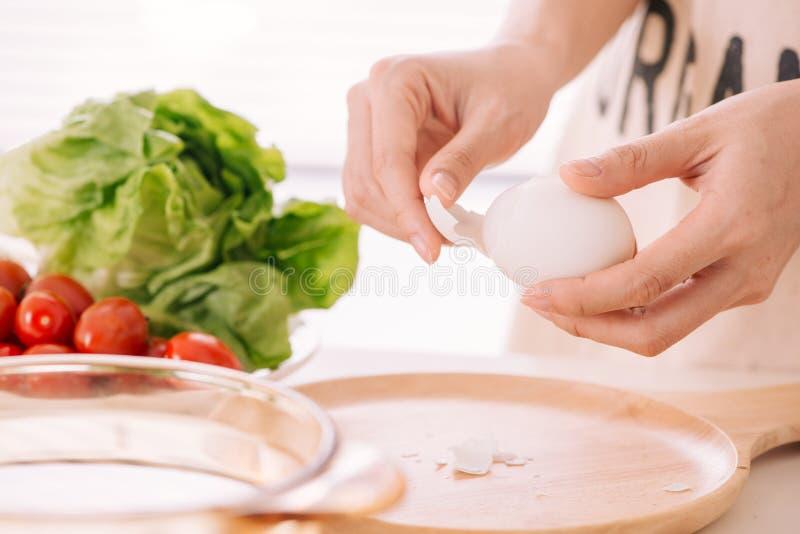 Le mani femminili sta sgusciando le uova del pollo La donna prepara il breakf immagine stock