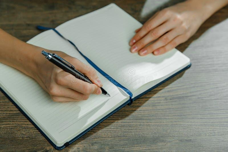 Le mani femminili stanno scrivendo in un taccuino fotografia stock libera da diritti