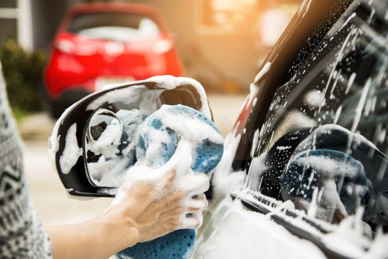 Le mani femminili tengono con l'automobile blu di lavaggio della spugna immagini stock libere da diritti