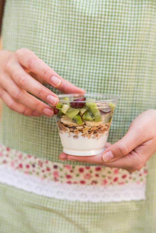 Le mani femminili tengono il yogurt con frutta ed i muesli fotografia stock libera da diritti