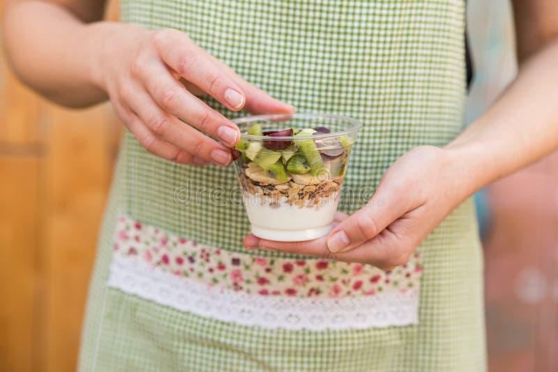 Le mani femminili tengono il yogurt con frutta ed i muesli immagini stock libere da diritti