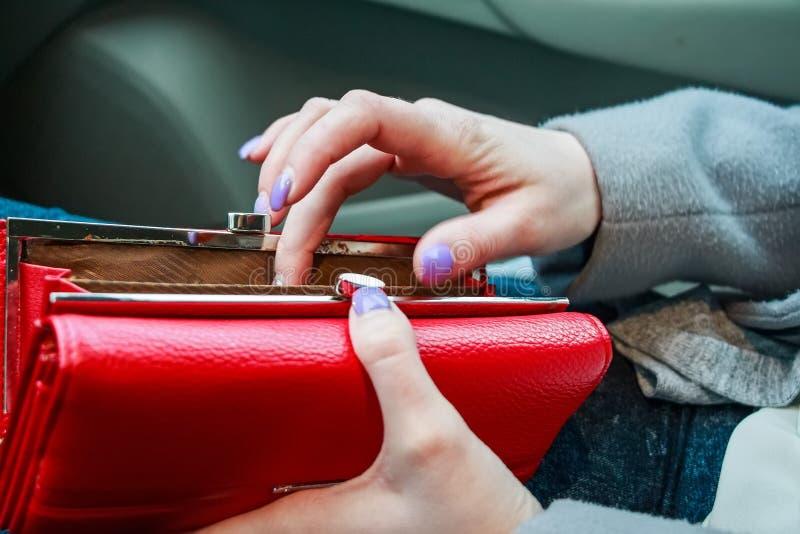 Le mani femminili tengono la borsa rossa moderna dei soldi per le donne fotografie stock