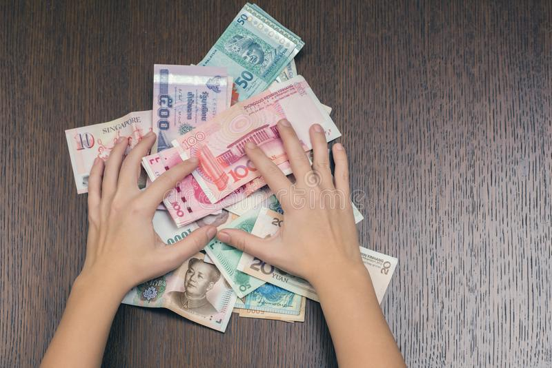 Le mani femminili tengono un pacco dei fondi Sud-est asiatico urgente alla tavola di legno Concetto di corruzione fotografie stock