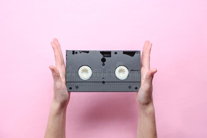 Le mani femminili tiene la videocassetta fotografie stock