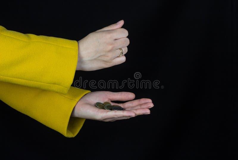 Le mani femminili in un cappotto giallo versano le monete da una mano ad un altro, il fondo nero, primo piano fotografie stock