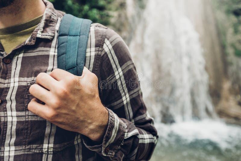 Le mani irriconoscibili dell'uomo del viaggiatore tiene la cinghia dello zaino sul fondo della cascata che fa un'escursione il co immagini stock