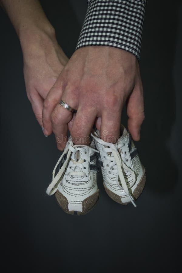 Le mani, la madre ed il padre della famiglia passano i bottini del neonato della tenuta fotografie stock