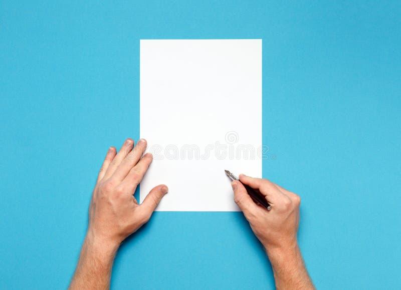 Le mani maschii è pronte per il disegno con la penna, vista superiore sulla superficie del blu Concetto di creatività fotografia stock libera da diritti