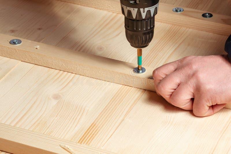 Le mani maschii avvitano i blocchi di legno ai bordi con un cacciavite fotografie stock
