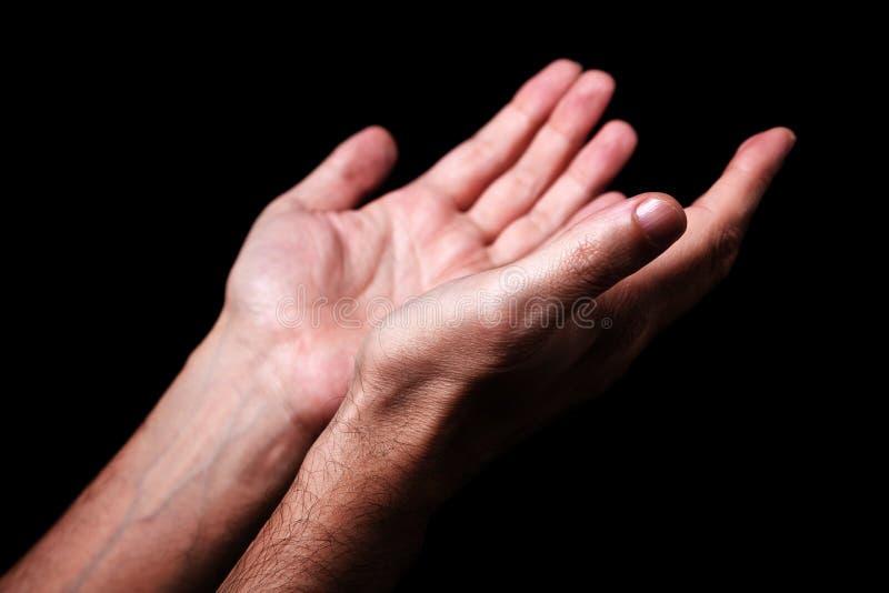 Le mani maschii che pregano con le palme su arma steso Priorità bassa nera immagine stock