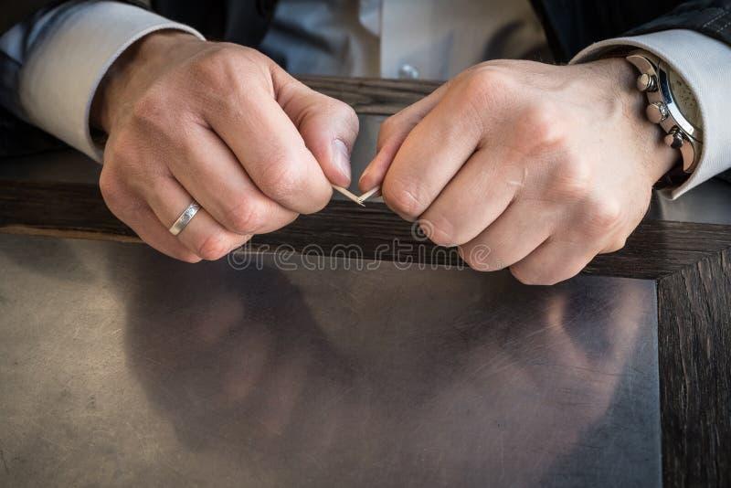 Le mani maschii del primo piano rompono gli stuzzicadenti fotografia stock
