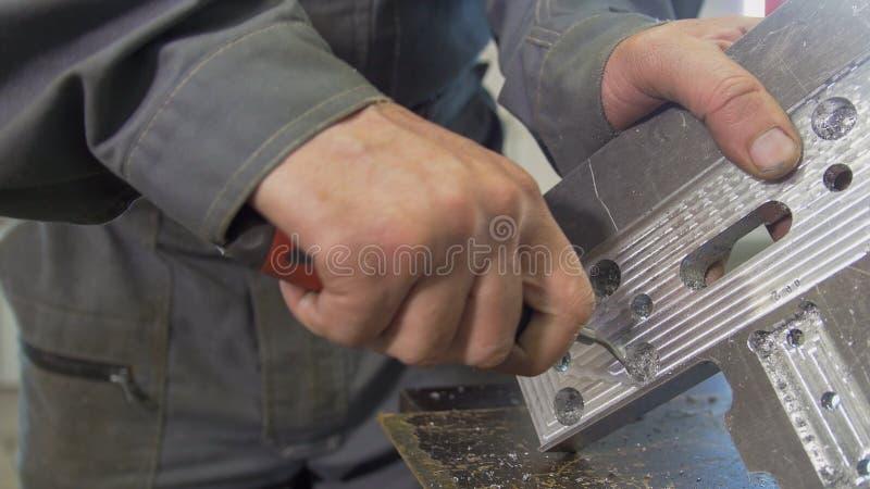 Le mani maschii fa la smussatura rimuovendo le sbavature sul pannello del metallo con una ruspa spianatrice fotografie stock