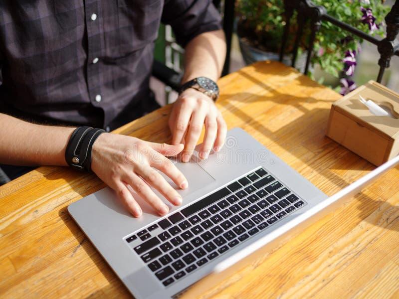 Le mani maschii stanno funzionando dietro un computer portatile Primo piano immagini stock