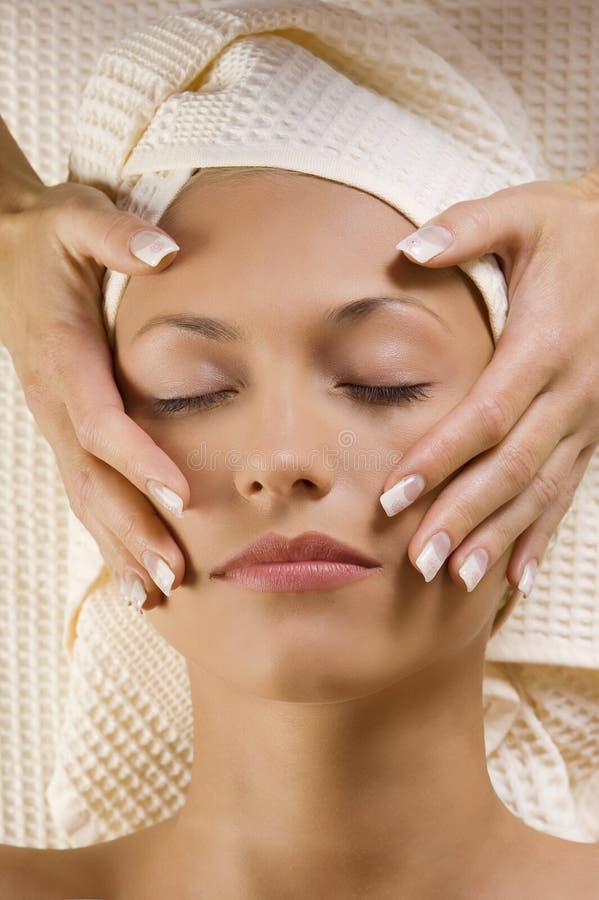Le mani massaggiano vicino alla testa immagini stock