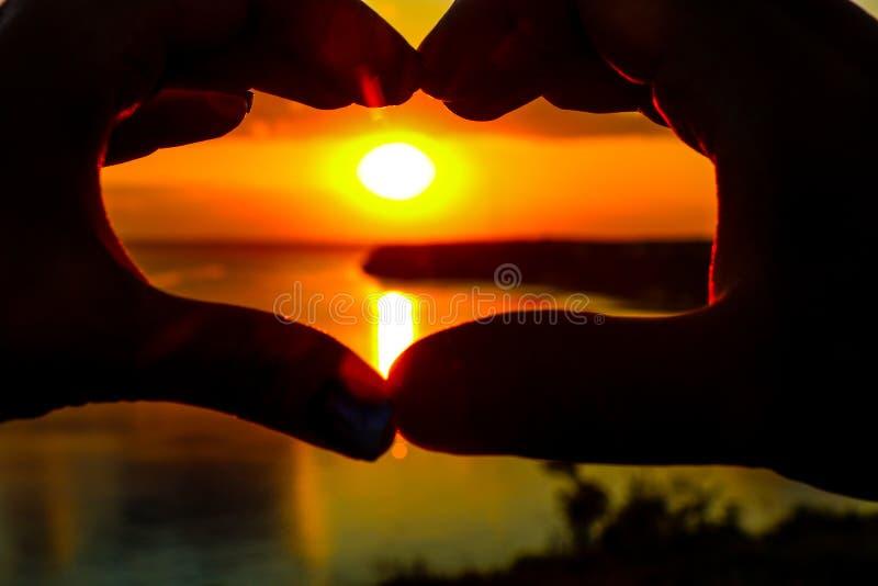 Le mani mostrano la forma del cuore contro il tramonto fotografie stock libere da diritti