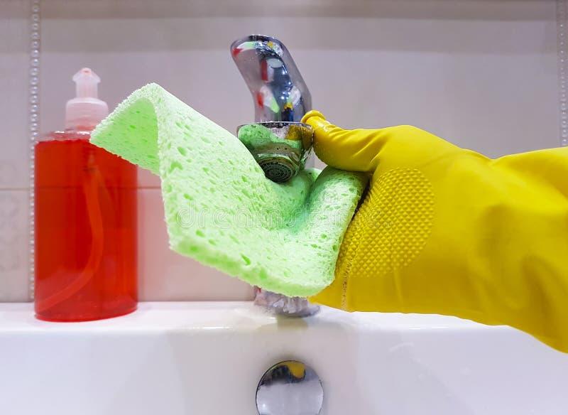 Le mani nel pulitore giallo del lavandino della domestica del lavaggio dei guanti nel lavaggio ceramico del bagno funzionano fotografie stock libere da diritti