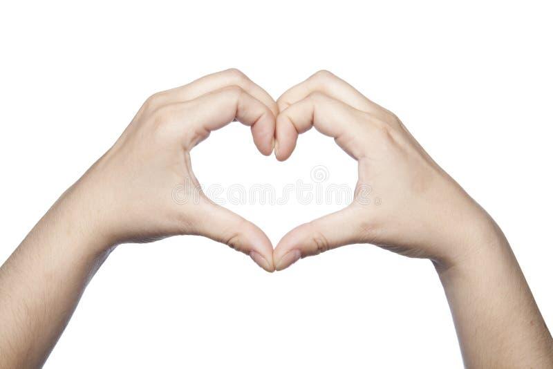 Le mani piegate sotto forma di un cuore indicano l'amore immagini stock