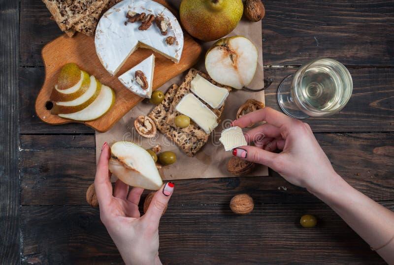 Le mani prende la pace di formaggio e della pera dalla tavola con alimento immagini stock libere da diritti