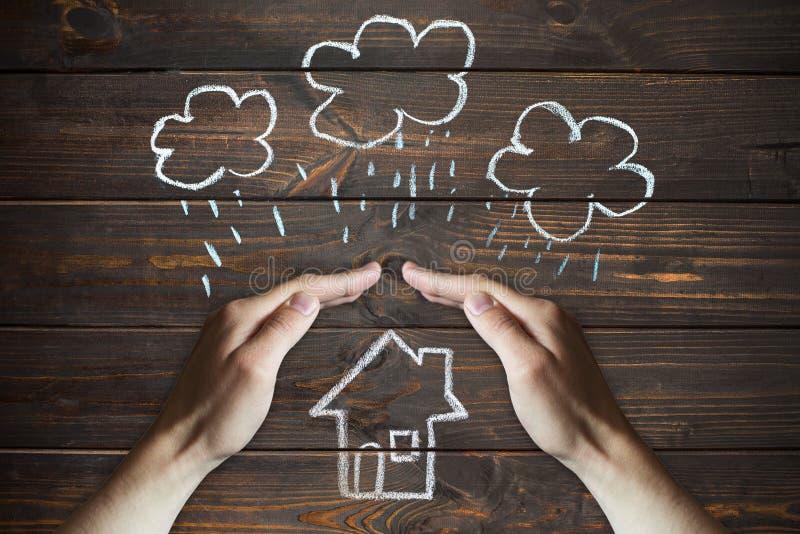 Le mani protegge una casa dagli elementi - pioggia o tempesta fotografie stock libere da diritti