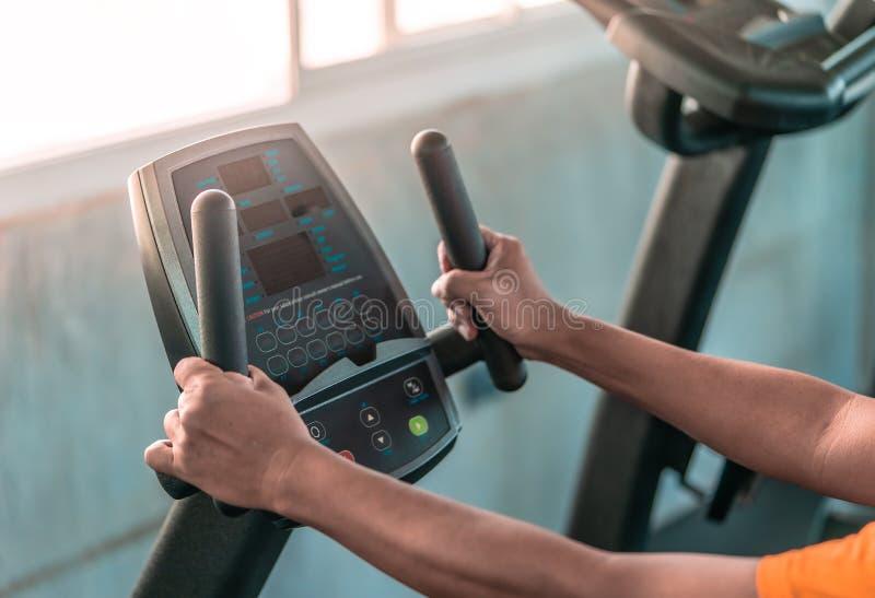 Le mani senior sta risolvendo sulla macchina di forma fisica per il concetto sano dell'anziano immagine stock