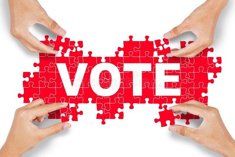 Le mani sistemano il puzzle con il testo di voto fotografia stock