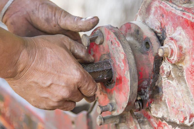 Le mani sono parti separate macchina e bullone dell'inserzione fotografie stock libere da diritti