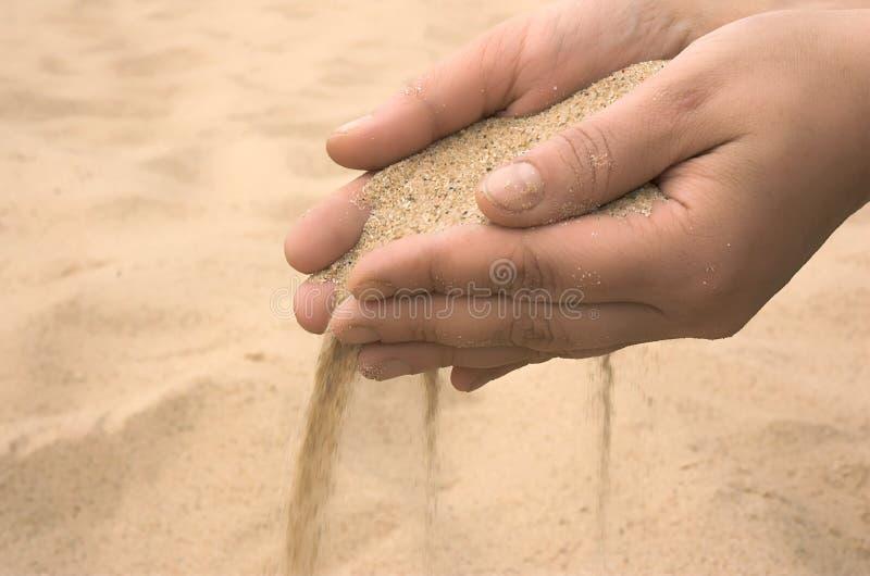Le mani spargono la sabbia immagini stock libere da diritti