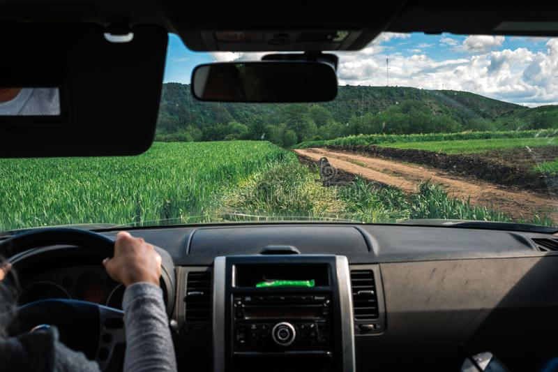 Le mani sull'interno del volante di un'automobile, strada non asfaltata dell'autista della donna del campo, fuori strada, fuori d fotografie stock